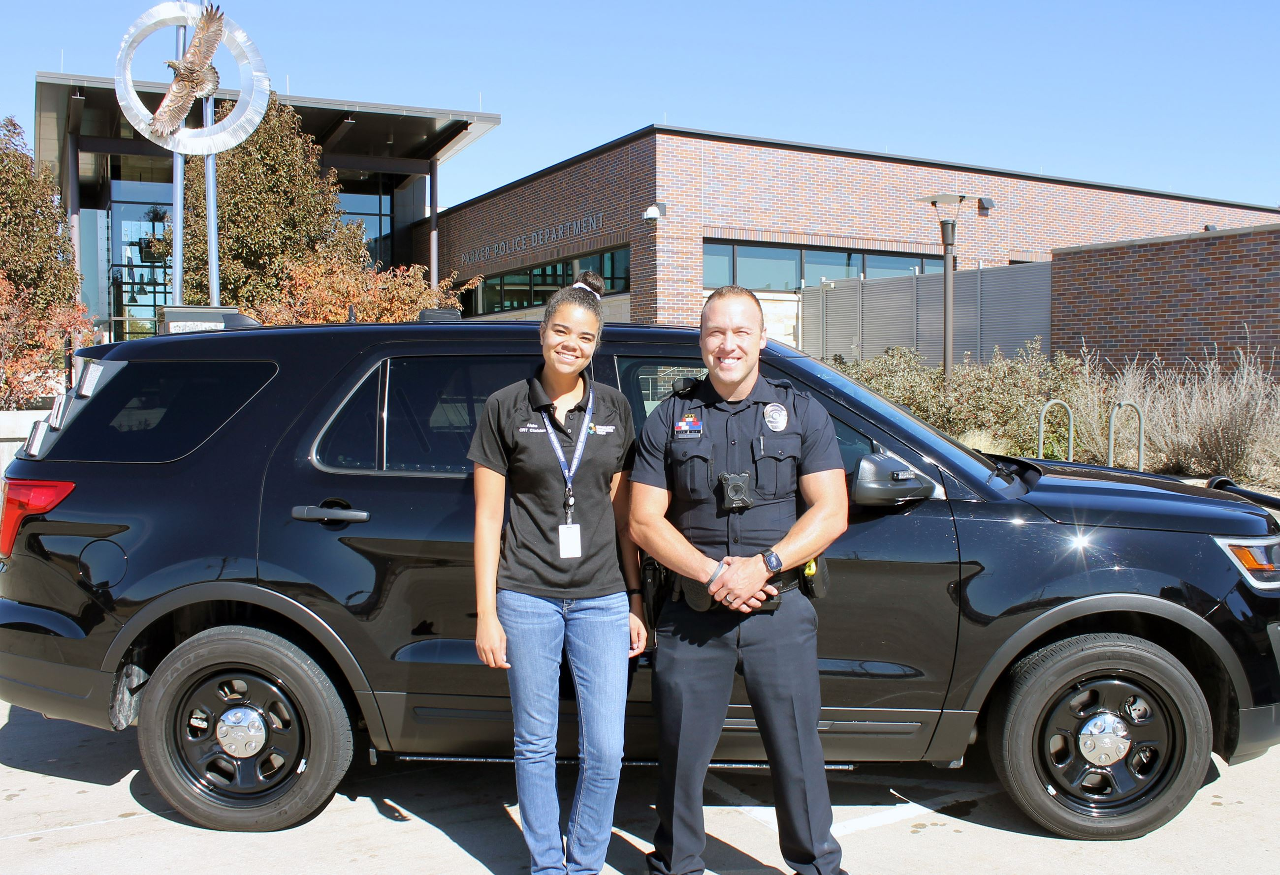 Officer Biles and Clinician Henry standing in front of their patrol car